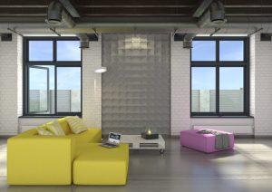 Model Pixels - panel w kolorze szarym zdobi ścianę pomiędzy dwoma dużymi oknami. Reszta ściany to biała cegiełka. Na podłodze stoi duża, żółta kanapa, wrzosowy podnóżek i stolik kawowy.